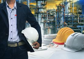 picture of refinery  - engineering man standing with white safety helmet against oil refinery in petrochemical industry - JPG
