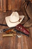 stock photo of pistols  - A cowboy hat black powder pistol and boots on a wooden background - JPG
