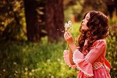 stock photo of country girl  - child girl dressed as fairytale princess playing with blow balls in summer forest - JPG