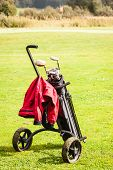 image of golf bag  - a wheeled golf bag full of golf clubs of a vibrant golf course - JPG