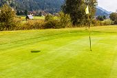 picture of flag pole  - a golf hole with a flag pole in a beautiful golf course - JPG
