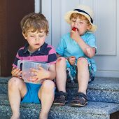 foto of strawberry blonde  - Two little friends sibling boys eating fresh organic strawberries in domestic garden on warm summer sunny day - JPG
