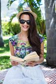 picture of palm-reading  - Smiling beautiful brunette sitting and reading a book with palm tree behind her - JPG