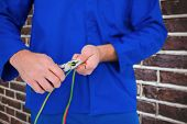 stock photo of pliers  - Electrician cutting wire with pliers against red brick wall - JPG