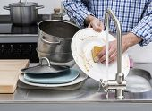 image of sink  - Man washing dishes in kitchen sink faucet with flowing water - JPG