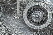 stock photo of flush  - Flushing water in a stainless steel kitchen sink - JPG