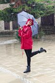 picture of dancing rain  - Young beautiful Caucasian woman with an umbrella dressed in Red and dancing in the rain.