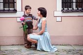 image of congrats  - Little boy giving flower to his mom outdoors - JPG