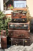 stock photo of old suitcase  - Old vintage retro used leather suitcases stacked and placed one on another in house backyard - JPG