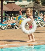 picture of pool ball  - little cute girl playing near the pool with a ball - JPG