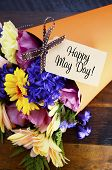 pic of may-flower  - Happy May Day traditional gift of Spring Flowers in orange paper cone on dark wood table - JPG