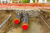 image of sandbag  - Newly laid pipe are passing under the road trough sandbag wall in trench - JPG