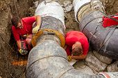 picture of pipe-welding  - Metal workers are grinding first weld on new pipeline - JPG