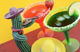 stock photo of mexican fiesta  - Happy Cinco de Mayo colorful party theme with bright color margarita drinks on red wood table and yellow background - JPG