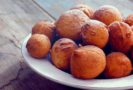 stock photo of sprinkling  - Sweet fried round doughnuts sprinkled with sugar powder on a plate - JPG