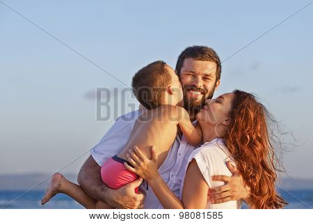 Portrait Of Positive Family On The Sunset Beach
