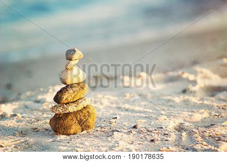 poster of Zen Stones on beach for perfect meditation. Calm zen meditate background with rock pyramid on sand beach symbolizing stability, harmony, balance. Shallow depth of field. Sea pebbles tower closeup.
