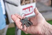 Cropped View Of Saleman Holding Keys Of New House, House For Sale Concept poster