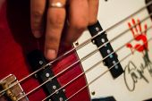 Bass Guitar In Playing Musician Hands Close-up. Focus On Bass Guitar Neck In Player Hands. Unrecogin poster