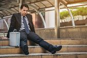 Desperate Businessman Sitting Hopelessly On Stair Floor poster