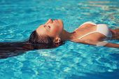 Portrait Of Beautiful Tanned Woman In White Swimwear Relaxing In Swimming Pool Spa. Hot Summer Day A poster