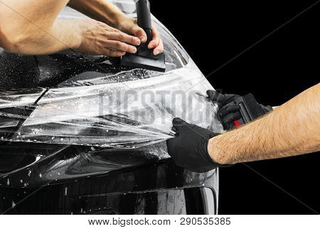 poster of Car Wrapping Specialist Putting Vinyl Foil Or Film On Car. Protective Film On The Car. Applying A Pr