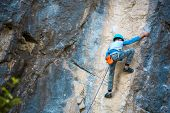 A Child Climber Climbs On A Rock. The Boy In The Helmet Climbs Up The Cliff. Strong Kid Overcomes A  poster