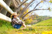 Asian Kid Girl Sitting Outdoor In Fallen Leaves At Autumn In The Park, Happy And Relax In Summertime poster