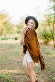 Beautiful Young Girl With Blond Hair In A Suede Jacket With Fringed And Black Felt Hat In The Countr poster