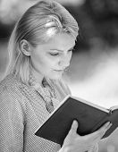 Girl Concentrated Sit Park Read Book Nature Background. Reading Inspiring Books. Female Literature.  poster