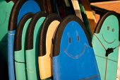 Set Of Different Color Surf Soft Boards With Smile For Beginers In A Stack By Ocean. Bali. Indonesia poster