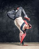 Hip-hop Style Dancer Performs Breakdance Acrobatic Elements. Studio Photo Against A Dark Textured Wa poster