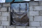 Unfinished House Of Gray Brick And Window Closed By Cellophane poster