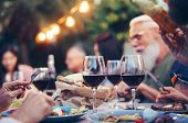 Happy Family Eating And Drinking Red Wine At Dinner Barbecue Party Outdoor - Mature And Young People poster