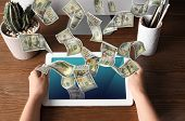 Man With Modern Tablet And Flying Dollar Banknotes At Table, Closeup. People Make Money Online poster