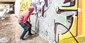 Street Artist Painting Colorful Graffiti On Public Wall - Modern Art Concept With Urban Guy Performi poster