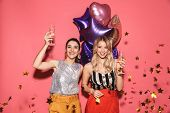 Photo of two fashionable women 20s in stylish outfit holding festive balloons and drinking champagne poster