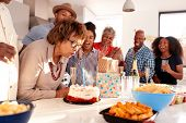 Senior black woman blowing out the candle on birthday cake during a celebration with her family poster