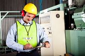 image of officer  - male occupational health and safety officer inside factory doing inspection - JPG