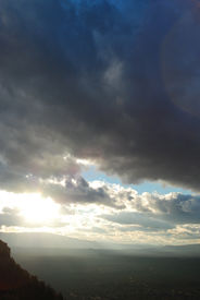 foto of sun rays  - Storm clouds rolling in over the mountains show a break where the sun shines through. ** Note: Slight graininess, best at smaller sizes - JPG