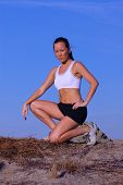 picture of bare midriff  - beautiful young woman jogger kneeling on side of path outlined against blue sky - JPG