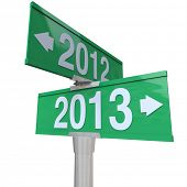 Green two-way road signs pointing from 2012 to 2013 to symbolize change to new year