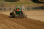 stock photo of horse plowing  - preparing the arena with tractor plow for equestrian competition  - JPG