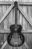 Monochrome Vintage Acoustic Guitar On Fence