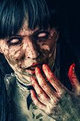 foto of zombie  - Scary zombie woman with white eyes and bloody hand - JPG