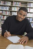 Portrait of an African American male student making notes in the college library