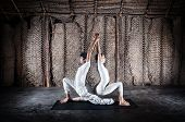 picture of surya  - Couple yoga of woman and man doing ashwa sanchalanasana lunge pose in white cloth in yoga hall Varkala Kerala India - JPG