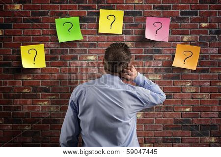 Choice and decisions: businessman thinking with question marks written on adhesive notes stuck to a  poster