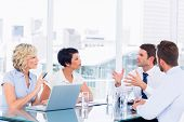 image of half-dressed  - Smartly dressed young executives sitting around conference table in office - JPG