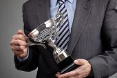 stock photo of award-winning  - Businessman celebrating with trophy award for success in business or first place sporting championship win - JPG
